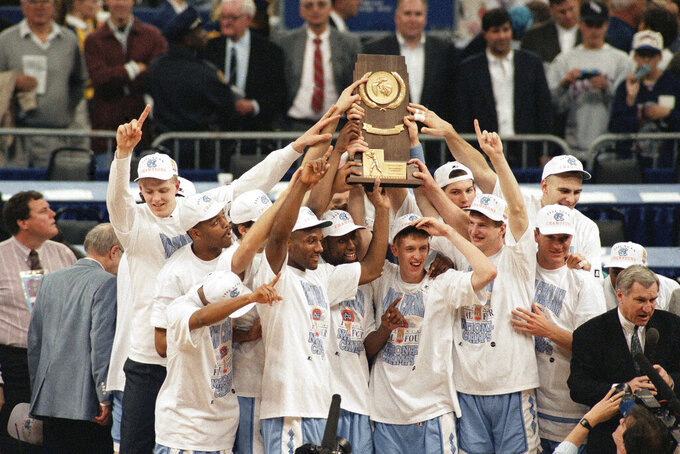 FILE - In this Monday, April 5, 1993, file photo, North Carolina poses with the trophy after defeating Michigan 77-71 in the NCAA Final Four Championship game at the Superdome in New Orleans, La. At far right is coach Dean Smith. Smith won his second national championship, and like the first title he won at the Superdome, this one wasn't sealed until somebody made a costly, almost unbelieveable, error. (AP Photo/Bob Jordan, File)