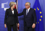 European Commission President Jean-Claude Juncker, right, greets British Prime Minister Theresa May on arrival at EU headquarters in Brussels, Wednesday, Nov. 21, 2018. (AP Photo/Olivier Matthys)