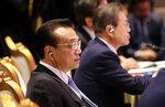 Chinese Premier Li Keqiang, left, and South Korean President Moon Jae-in wait to speak at the Association of Southeast Asian Nations (ASEAN) Plus Three summit in Nonthaburi, Thailand, Monday, Nov. 4, 2019. (AP Photo/Aijaz Rahi)
