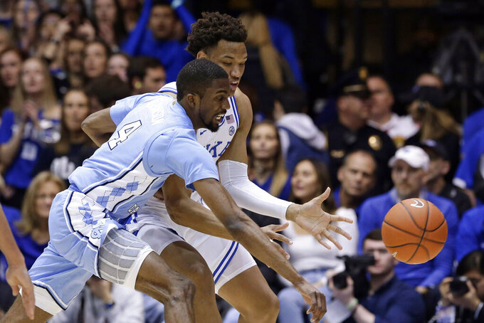 North Carolina guard Brandon Robinson (4) and Duke forward Wendell Moore Jr. chase the ball during the first half of an NCAA college basketball game in Durham, N.C., Saturday, March 7, 2020. (AP Photo/Gerry Broome)