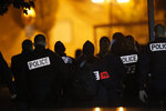 French police officers gather outside a high school after a history teacher who opened a discussion with students on caricatures of Islam's Prophet Muhammad was beheaded, Friday, Oct. 16, 2020 in Conflans-Saint-Honorine, north of Paris. Police have shot the suspected killer dead. (AP Photo/Michel Euler)