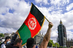 A demonstrator walks holding an Afghanistan flag, during a protest at Parliament Square in London, Wednesday, Aug. 18, 2021. British Prime Minister Boris Johnson is set to update lawmakers Wednesday about the evacuation of British nationals and local allies from Afghanistan. Big Ben's clock tower shrouded in scaffolding, right. (AP Photo/ Alberto Pezzali)