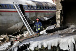 This photo provided by Mizan News Agency, shows an Iranian rescue works at the site of a Boeing 707 cargo plane crash, at Fath Airport about 40 kilometers (25 miles) west of Tehran, Iran, Monday, Jan. 14, 2019. An Iranian emergency management official has told state TV that 16 people were on board a Boeing 707 cargo plane that crashed west of Tehran and that there is only one known survivor. (Hasan Shirvani/Mizan News Agency via AP)