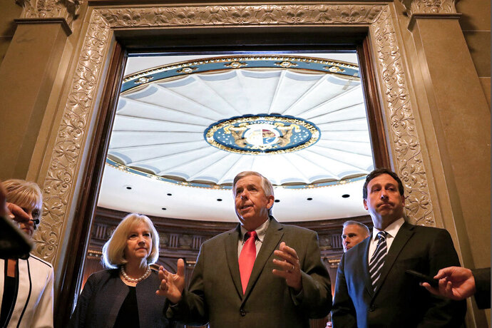 FILE - In this June 6, 2018 file photo, Missouri Gov. Mike Parson, center, addresses the media as St. Louis Mayor Lyda Krewson, left, and St. Louis County Executive Steve Stenger, listen, in Jefferson City, Mo. A bill requiring St. Louis gun dealers to alert police when a firearms purchase is denied because of a criminal background check is the latest step in addressing violence in a city beset by gun crimes. The bill adopted Friday, Nov. 1, 2019, awaits the mayor's signature. Both of Missouri's big cities, St. Louis and Kansas City, have among the highest homicide rates in the nation, and both are seeking to address the problem through tougher gun laws. (Christian Gooden/St. Louis Post-Dispatch via AP File)