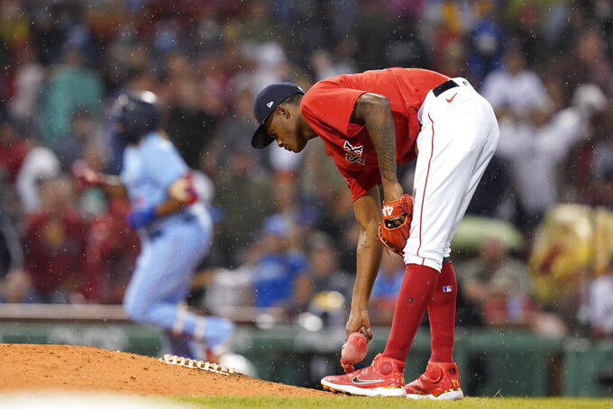 Boston Red Sox relief pitcher Phillips Valdez picks up the rosin bag as Toronto Blue Jays' Vladimir Guerrero Jr. rounds third after hitting a three-run home run during the fifth inning of a baseball game at Fenway Park, Thursday, July 29, 2021, in Boston. (AP Photo/Elise Amendola)