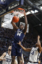 Georgetown center Qudus Wahab (34) gets a dunk over Butler forward Bryce Golden (33) and guard Khalif Battle (4) in the second half of an NCAA college basketball game in Indianapolis, Saturday, Feb. 15, 2020. Georgetown defeated Butler 73-66. (AP Photo/Michael Conroy)