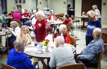 Seniors mingle and eat a celebratory cake as Muscle Shoals Senior Living Center opens to guests on Tuesday, June 8, 2021 in Muscle Shoals, Ala. (Dan Busey/The TimesDaily via AP)