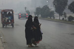 People cross a road engulfs in smog in Lahore, Pakistan, Friday, Nov. 22, 2019. Tens of thousands of people in Pakistan's eastern city are at risk of respiratory disease because of poor air quality related to thick smog hanging over the region, an international rights group said Friday. (AP Photo/K.M. Chaudary)