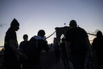 Demonstrators are seen in silhouette during a march across the Brooklyn Bridge as part of a solidarity rally calling for justice over the death of George Floyd Monday, June 1, 2020, in the Brooklyn borough of New York. Floyd died after being restrained by Minneapolis police officers on May 25. (AP Photo/Wong Maye-E)