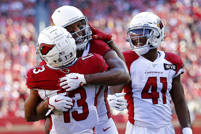 Arizona Cardinals wide receiver Larry Fitzgerald, center, celebrates with wide receiver Christian Kirk (13) and running back Kenyan Drake (41) after scoring against the San Francisco 49ers during the first half of an NFL football game in Santa Clara, Calif., Sunday, Nov. 17, 2019. (AP Photo/Josie Lepe)