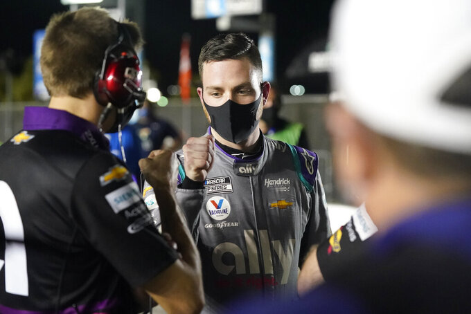 Alex Bowman, right, gets a fist bump from one of his crew members after winning the pole position for the NASCAR Daytona 500 auto race during qualifying at Daytona International Speedway, Wednesday, Feb. 10, 2021, in Daytona Beach, Fla. (AP Photo/John Raoux)