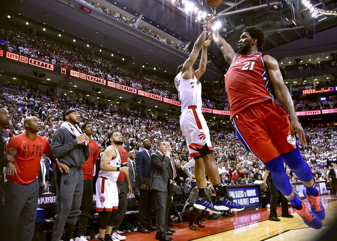 FILE - In this Sunday, May 12, 2019, file photo, Philadelphia 76ers center Joel Embiid (21) fails to stop Toronto Raptors forward Kawhi Leonard's (2) last-second basket during the second half of an NBA Eastern Conference semifinal basketball game in Toronto. (Frank Gunn/The Canadian Press via AP, File)
