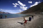 In this July 22, 2011, file photo, children play cricket by Pangong Lake, near the India-China border in Ladakh, India. Indian officials say Indian and Chinese soldiers are in a bitter standoff in the remote and picturesque Ladakh region, with the two countries amassing soldiers and machinery near the tense frontier. The officials said the standoff began in early May when large contingents of Chinese soldiers entered deep inside Indian-controlled territory at three places in Ladakh, erecting tents and posts. (AP Photo/Channi Anand, File)