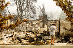 A man examines residences destroyed by the Almeda Fire at the Parkview Townhomes in Talent, Ore., on Wednesday, Sept. 16, 2020. (AP Photo/Noah Berger)