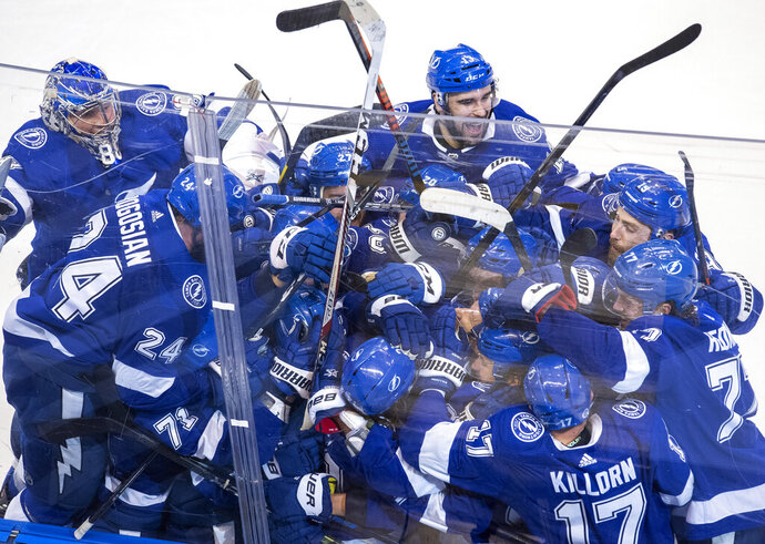 The Tampa Bay Lightning celebrate after Brayden Point (21) scored against the Columbus Blue Jackets during the fifth overtime in Game 1 of an NHL hockey Stanley Cup first-round playoff series, Tuesday, Aug. 11, 2020, in Toronto. (Frank Gunn/The Canadian Press via AP)