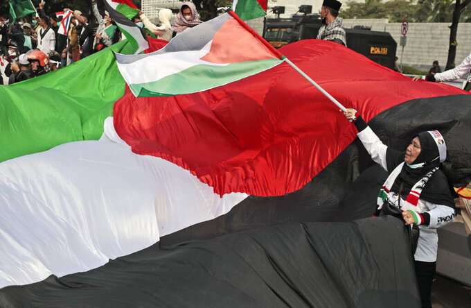 Protesters wave Palestinian flags during a rally against Israel's attacks on Gaza, outside the U.S. Embassy in Jakarta, Indonesia, Friday, May 21, 2021. (AP Photo/Dita Alangkara)