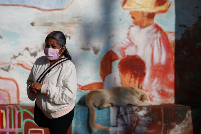 A woman rubs antibacterial gel into her hands as she waits in a distanced line to get tested for COVID-19 at a mobile diagnostic tent in San Gregorio Atlapulco in the Xochimilco district of Mexico City, Wednesday, July 22, 2020. The capital's health secretariat has erected mobile testing units in the areas of the city hardest hit by the coronavirus pandemic, but with test supplies limited - on Wednesday only 20 were available in San Gregorio Atlapulco - some symptomatic people end up waiting in line on multiple days before successfully getting a test. (AP Photo/Rebecca Blackwell)
