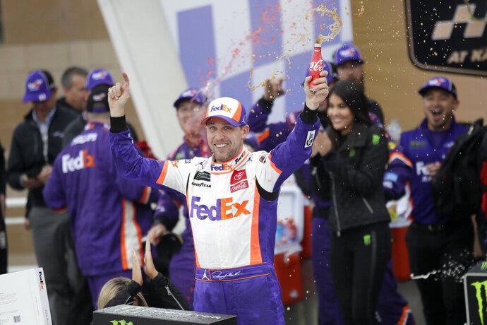 Denny Hamlin (11) celebrates after winning a NASCAR Cup Series auto race at Kansas Speedway in Kansas City, Kan., Sunday, Oct. 20, 2019. (AP Photo/Orlin Wagner)