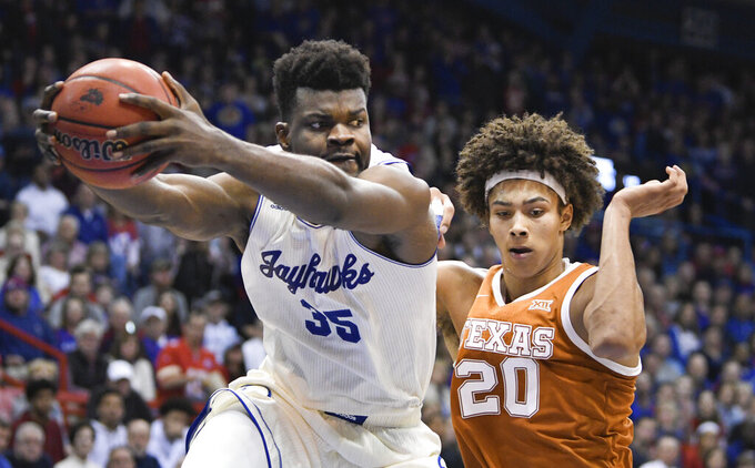 Kansas center Udoka Azubuike (35) pulls down a rebound in front of Texas forward Jericho Sims (20) during the second half of an NCAA college basketball game in Lawrence, Kan., Monday, Feb. 3, 2020. (AP Photo/Reed Hoffmann