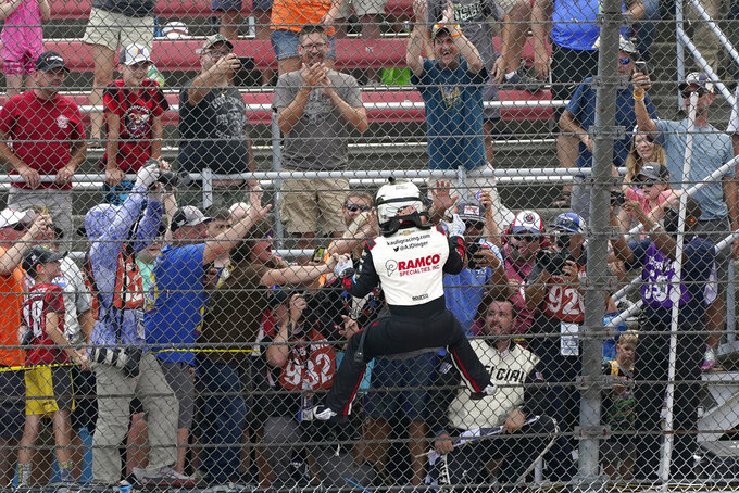 A.J. Allemdinger climbs the fence after winning the NASCAR Xfinity Cup Series auto race at Michigan International Speedway, Saturday, Aug. 21, 2021, in Brooklyn, Mich. (AP Photo/Carlos Osorio)