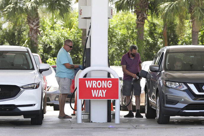 Drivers fuel up at BJ's in Boynton Beach, Fla.,  as they prepare for Hurricane Isaias on Friday, July 31, 2020.  Isaias is forecasted to stay east of the coast but it will bring winds and possible coasting flooding. (Amy Beth Bennett/South Florida Sun-Sentinel via AP)
