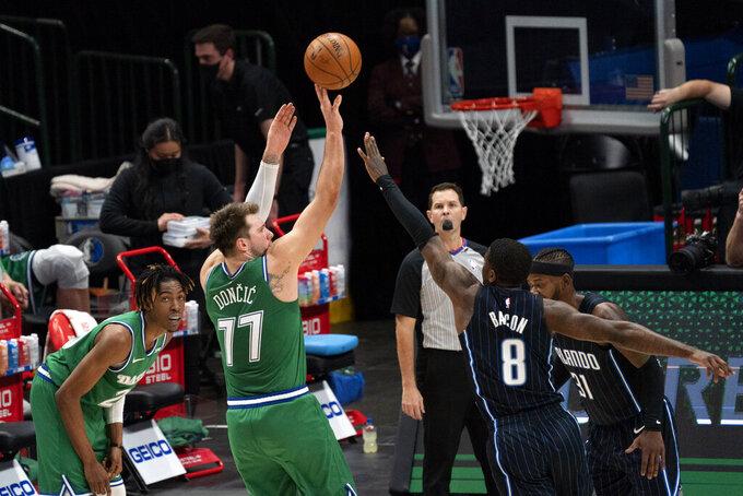 Dallas Mavericks guard Luka Doncic (77) shoots a three-point basket over Orlando Magic guard Dwayne Bacon (8) as Mavericks' forward Wes Iwundu looks on during the second half of an NBA basketball game, Saturday, Jan. 9, 2021, in Dallas. Dallas won 112-98. (AP Photo/Jeffrey McWhorter)