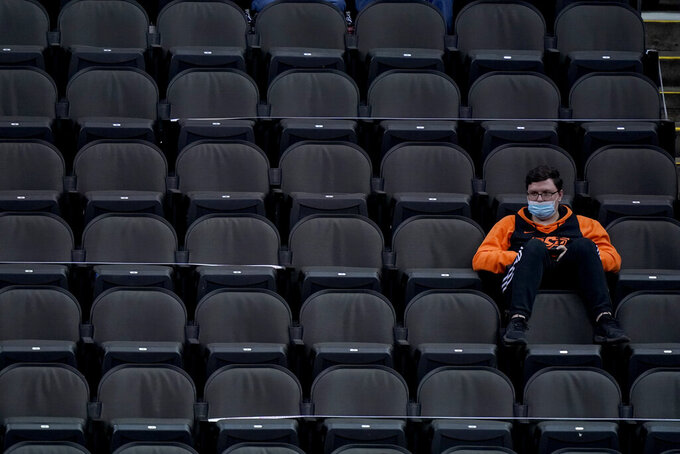 An Oklahoma State fan watches during the second half of an NCAA college basketball game between Baylor and Kansas State in the second round of the Big 12 men's tournament in Kansas City, Mo., Thursday, March 11, 2021. Baylor won 74-68. (AP Photo/Charlie Riedel)
