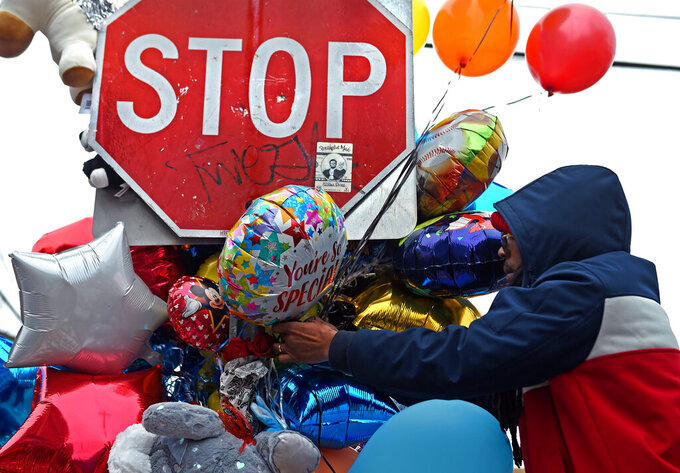 A man attaches more balloons to a memorial for Randell Jones on Monday, April 12, 2021 in Hartford.  Police said Randell Jones, 3, was riding in a car with his mother, other relatives and a man when another vehicle pulled along side them and someone opened fire on Saturday. Randell died in the shooting, which appeared to have targeted the man in the car, police said. (Brad Horrigan /Hartford Courant via AP)