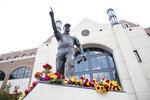 Flowers collect at the feet of Bobby Bowden's statue outside Doak Campbell Stadium in the hours following his death Sunday, August 8, 2021 in Tallahassee, Fla. Bobby Bowden, the folksy Hall of Fame coach who built Florida State into a college football dynasty that powered its way to a dozen conference titles and two national championships, died early Sunday, Aug. 8, 2021. He was 91.(Tori Lynn Schneider/Tallahassee Democrat via AP)