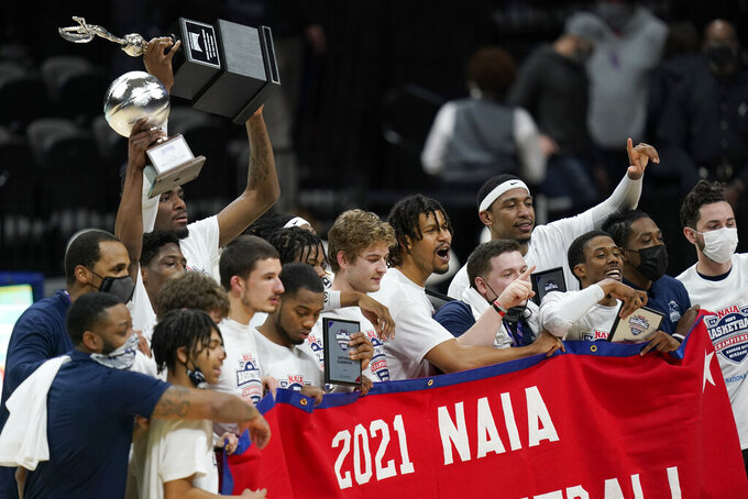 Shawnee State players celebrate after a win over Lewis-Clark State in the final of the NAIA men's college basketball tournament in Kansas City, Mo., Tuesday, March 23, 2021. (AP Photo/Orlin Wagner)