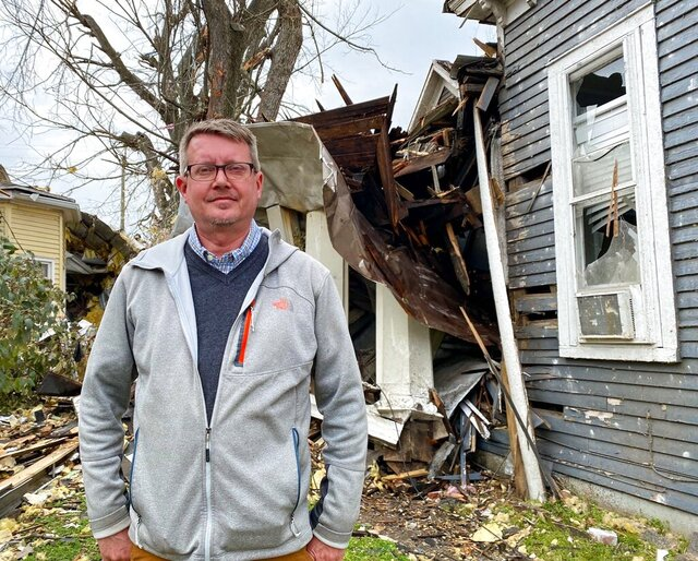 In this on March 10, 2020 photo, historian Robbie Jones stands in front of his damaged office building in East Nashville, Tenn., a week after a tornado pummeled the neighborhood. (Samantha Max/WPLN News via AP)