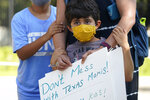 Luna Sendejo, 6, stands with his family as students and parents gather outside the Governor's Mansion to urge Gov. Greg Abbott to drop his opposition to public school mask mandates, Monday, Aug. 16, 2021, in Austin, Texas. The Texas Supreme Court has blocked mask mandates ordered by two of the nation's largest counties that defied Republican Gov. Greg Abbott as COVID-19 cases surge. (AP Photo/Eric Gay)