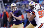 Washington quarterback Jake Browning, left, drops back to pass against Oregon State in the first half of an NCAA college football game Saturday, Nov. 17, 2018, in Seattle. (AP Photo/Elaine Thompson)
