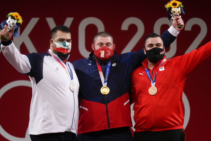 From left, silver medalist Alii Davoudi of Iranm gold medalist Lasha Talakhadze of Georgia and Man Asaad of Syria celebrate on the podium of the men's +109kg weightlifting event, at the 2020 Summer Olympics, Wednesday, Aug. 4, 2021, in Tokyo, Japan. (AP Photo/Luca Bruno)