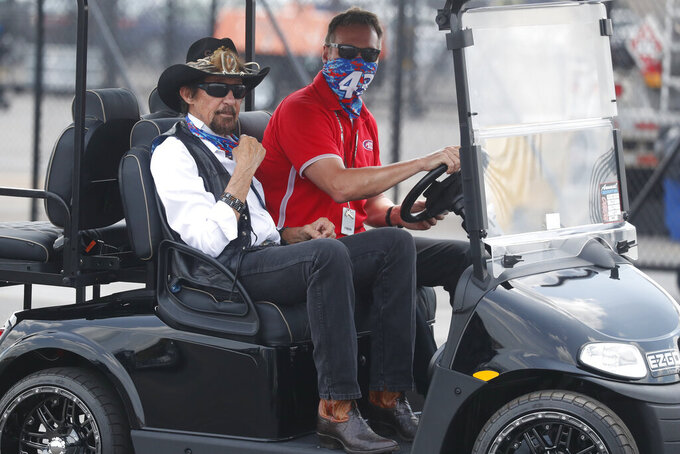 Owner of the race car of Bubba Wallace, former driver Richard Petty, left, rides a golf cart to the garage prior to the NASCAR Cup Series auto race at the Talladega Superspeedway in Talladega Ala., Monday June 22, 2020 (AP Photo/John Bazemore)