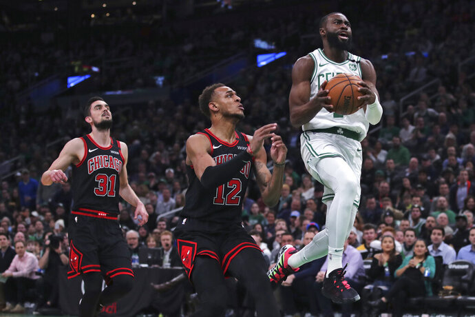 Boston Celtics guard Jaylen Brown (7) outruns Chicago Bulls guard Tomas Satoransky (31) and forward Daniel Gafford (12) on a drive to the basket during the first half of an NBA basketball game in Boston, Monday, Jan. 13, 2020. (AP Photo/Charles Krupa)