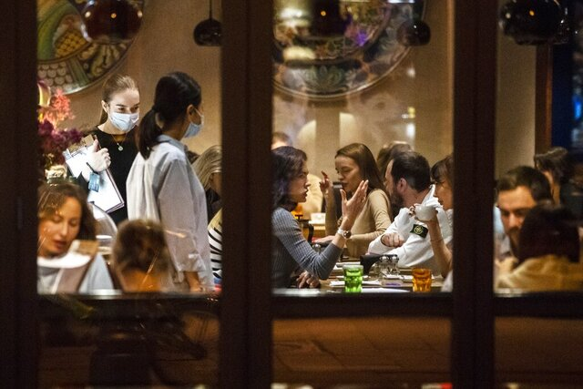 Customers sit in a restaurant at Patriarshiye Prudy, a hip restaurant and bar district in Moscow, Russia, late Friday, Oct. 16, 2020. The outbreak in Russia this month is breaking the records set in the spring, when a lockdown to slow the spread was put in place. But, as governments across Europe move to reimpose restrictions to counter rising cases, authorities in Russia are resisting shutting down businesses again. (AP Photo/Pavel Golovkin)