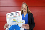 In this photo taken Wednesday, May 15, 2019, Vashon Island High School nurse Sarah Day holds information about measles vaccinations as she poses for a photo in Vashon Island, Wash. Since Day began communal living on Vashon Island more than 20 years ago, the registered nurse has been advocating for getting kids their shots against a loud contingent of anti-vaccine parents in the close-knit community of about 11,000 that's accessible only by ferry, a serene 20-minute ride from Seattle. And it may now be working, thanks to a