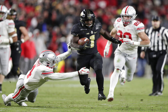 Purdue running back D.J. Knox (1) cuts between Ohio State safety Jordan Fuller (4) and linebacker Pete Werner (20) on his way to a touchdown during the second half of an NCAA college football game in West Lafayette, Ind., Saturday, Oct. 20, 2018. (AP Photo/Michael Conroy)