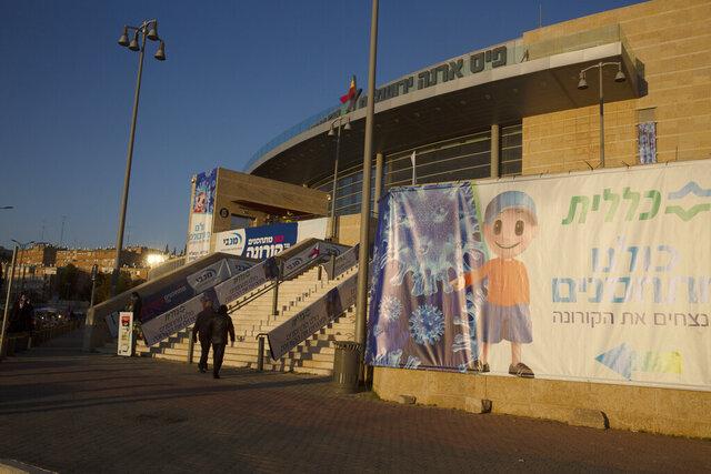 A couple enters a sports arena to receive the coronavirus vaccine in Jerusalem, Wednesday, Dec. 30, 2020. (AP Photo/Maya Alleruzzo)
