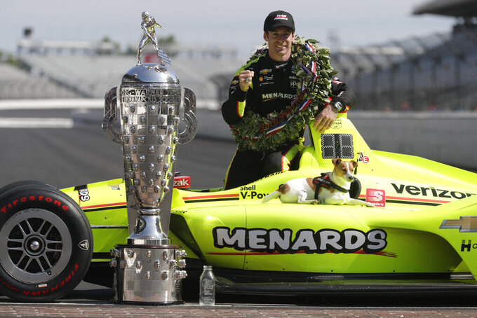 Simon Pagenaud, of France, winner of the 2019 Indianapolis 500 auto race, poses with his dog Norman during the traditional winners photo session at the Indianapolis Motor Speedway in Indianapolis, Monday, May 27, 2019. (AP Photo/Michael Conroy)