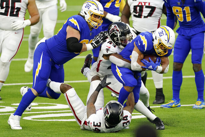 Los Angeles Chargers running back Austin Ekeler (30) is tackled by Atlanta Falcons linebacker Mykal Walker (43) during the first half of an NFL football game Sunday, Dec. 13, 2020, in Inglewood, Calif. (AP Photo/Ashley Landis)
