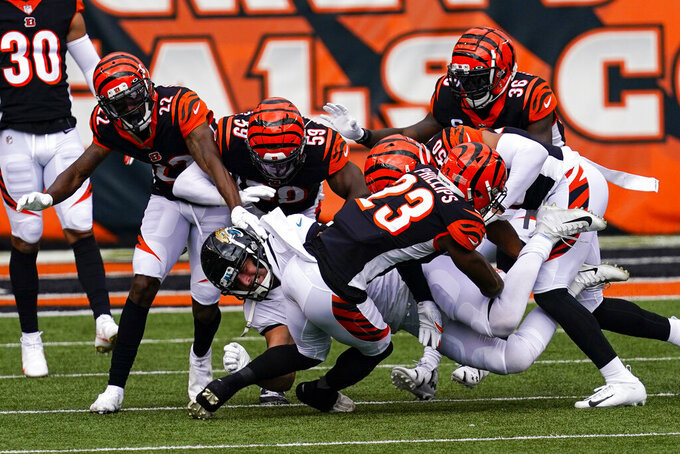 Jacksonville Jaguars tight end Tyler Eifert (88) is tackled by Cincinnati Bengals cornerback Darius Phillips (23), cornerback William Jackson (22), linebacker Akeem Davis-Gaither (59) and strong safety Shawn Williams (36) in the first half of an NFL football game in Cincinnati, Sunday, Oct. 4, 2020. (AP Photo/Bryan Woolston)