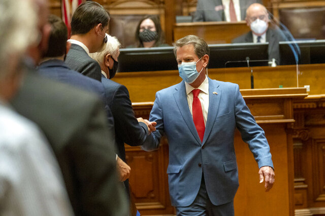 FILE - In this Friday, June 26, 2020, file photo, Georgia Gov. Brian Kemp is greeted as he visits the House Chambers on Sine Die, day 40, of the legislative session in Atlanta. Kemp says he hasn't yet weighed whether the state will take legal action against local governments trying to impose mask requirements. The Republican held a news conference Wednesday, July 1, 2020, before departing on a statewide tour to promote wearing a mask, but said he won't mandate it. (Alyssa Pointer/Atlanta Journal-Constitution via AP, File)