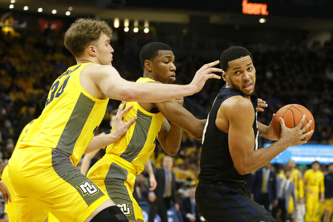 Butler's Bryce Nze, right, drives to the basket against Marquette defenders during the second half of an NCAA college basketball game Sunday, Feb. 9, 2020, in Milwaukee. (AP Photo/Aaron Gash)