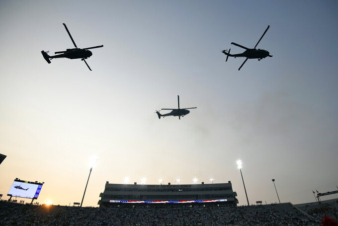 Helicopters fly over the stadium during the national anthem before an NCAA college football game between Austin Peay and Mississippi at Vaught-Hemingway Stadium in Oxford, Miss., Saturday, Sept. 11, 2021. (AP Photo/Bruce Newman)