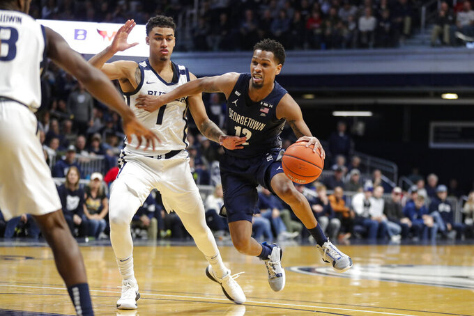 Georgetown guard Terrell Allen (12) goes around Butler forward Jordan Tucker (1) in the second half of an NCAA college basketball game in Indianapolis, Saturday, Feb. 15, 2020. Georgetown defeated Butler 73-66. (AP Photo/Michael Conroy)