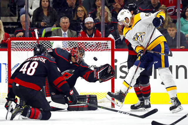 Nashville Predators' Austin Watson (51) redirects the puck past Carolina Hurricanes goaltender Petr Mrazek (34), of the Czech Republic, with Jordan Martinook (48) nearby during the second period of an NHL hockey game in Raleigh, N.C., Friday, Nov. 29, 2019. (AP Photo/Karl B DeBlaker)