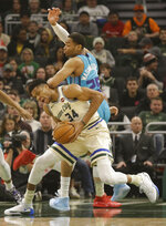 Charlotte Hornets' P.J. Washington (25) defends against the Milwaukee Bucks' Giannis Antetokounmpo during the first half of an NBA basketball game Saturday, Nov. 30, 2019, in Milwaukee. (AP Photo/Jeffrey Phelps)
