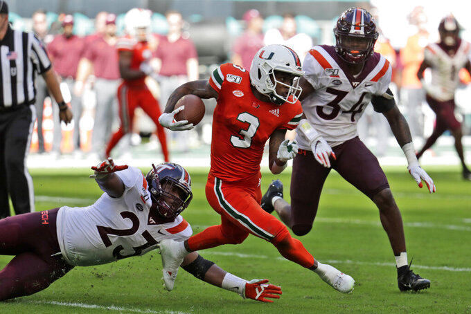 Miami wide receiver Mike Harley (3) runs as Virginia linebacker Rayshard Ashby (23) and linebacker Alan Tisdale (34) defend during the first half of an NCAA college football game, Saturday, Oct. 5, 2019, in Miami Gardens, Fla. (AP Photo/Lynne Sladky)